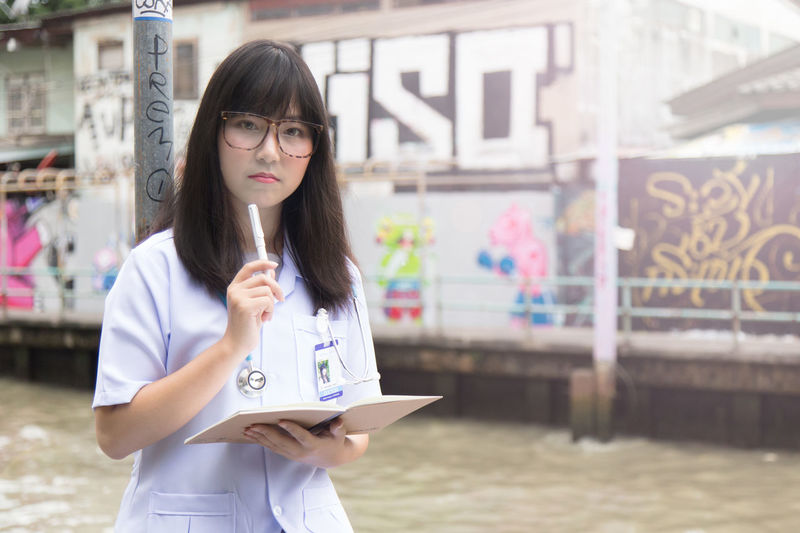 Portrait Of Female Doctor Holding Book Standing Outdoors