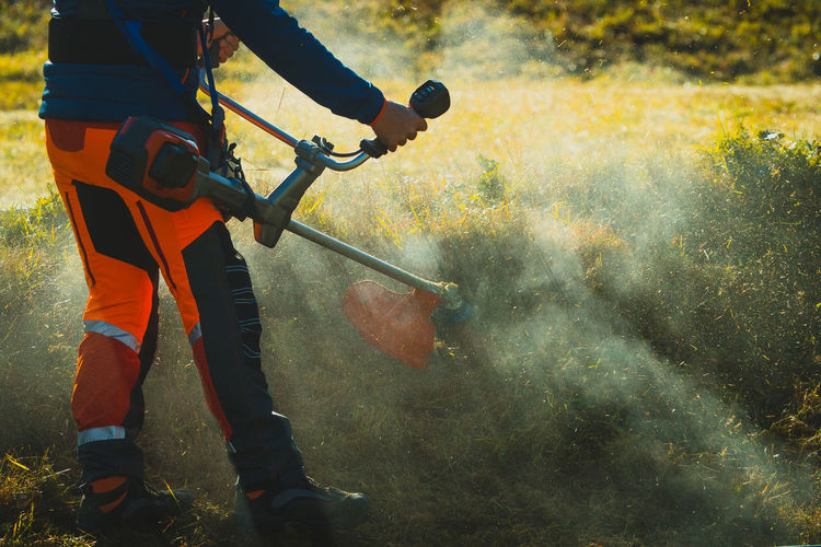 Low section of man sprinkling fertilizers while standing on field