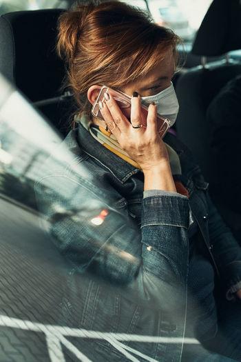 Woman wearing mask talking on phone sitting in car
