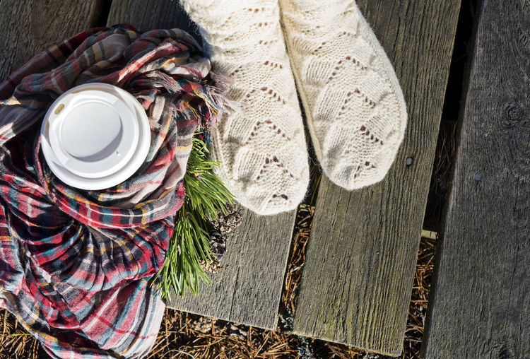 Hot coffee for take-away and female feet in warm knitted socks Autumn Checkered Estonia Fir Branch Kaberneeme Rand Nature Wanderlust Wintertime Checkered Scarf Coffee Cup Coffee To Go Cold Comfortable Cozy At Home Hot Drink Hygge Knitted Socks Neckerchief Christmastime Sunny Day Textile View From Above Walking Woman Legs Wood - Material