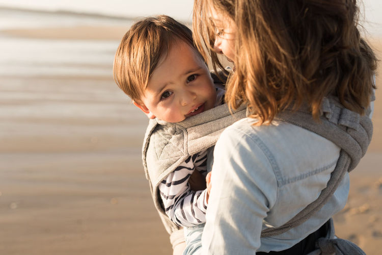 Mother carrying son while standing at beach