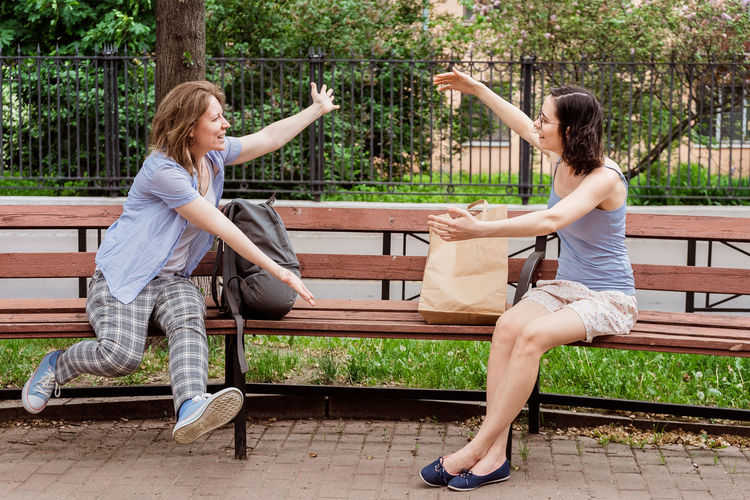 Friends meet each other in the park. greeting girls with social distancing