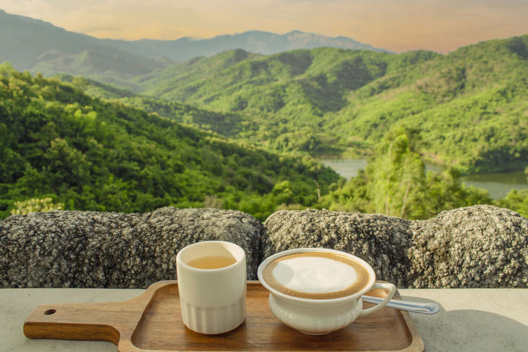 Coffee and cup on table against mountains
