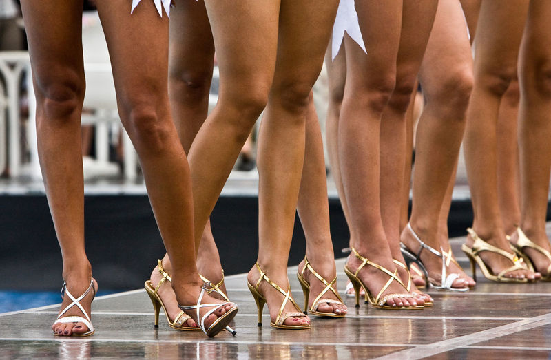 Low section of models wearing high heels while standing in fashion show