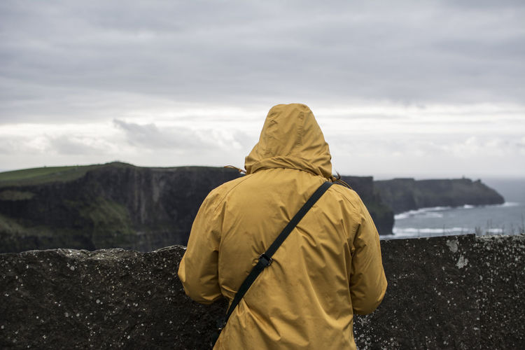 Rear view of woman wearing yellow warm clothing with cliff in background against cloudy sky