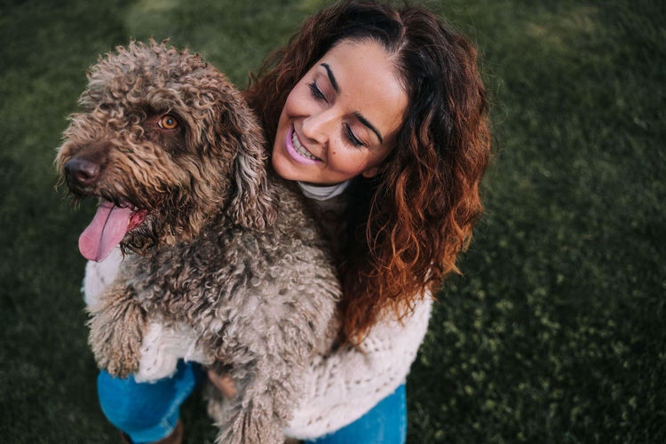High angle view of smiling woman holding dog on grassy land