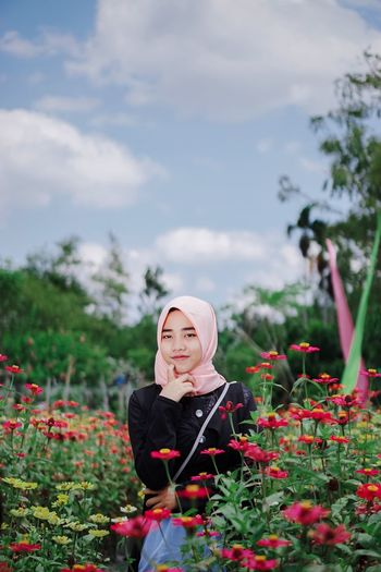 Portrait of young woman wearing hijab by flowering plants in park