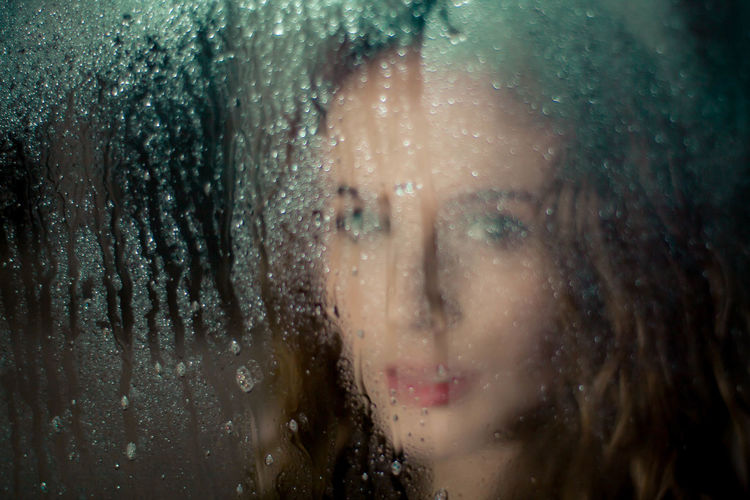 Close-up portrait of woman seen through wet window in rainy season