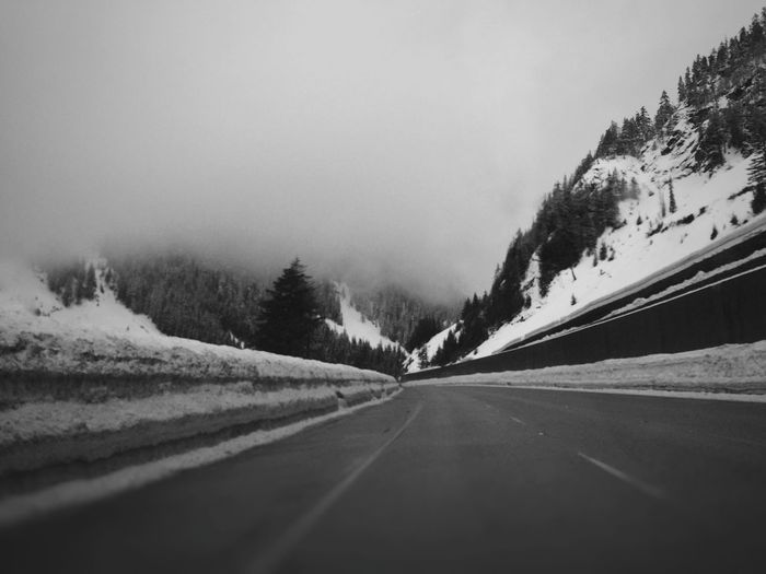 Road by mountains against clear sky during winter
