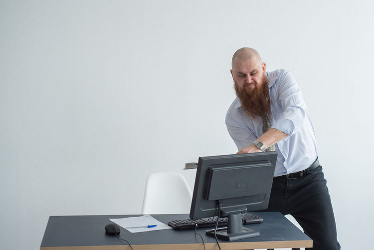 Man using laptop on table against wall