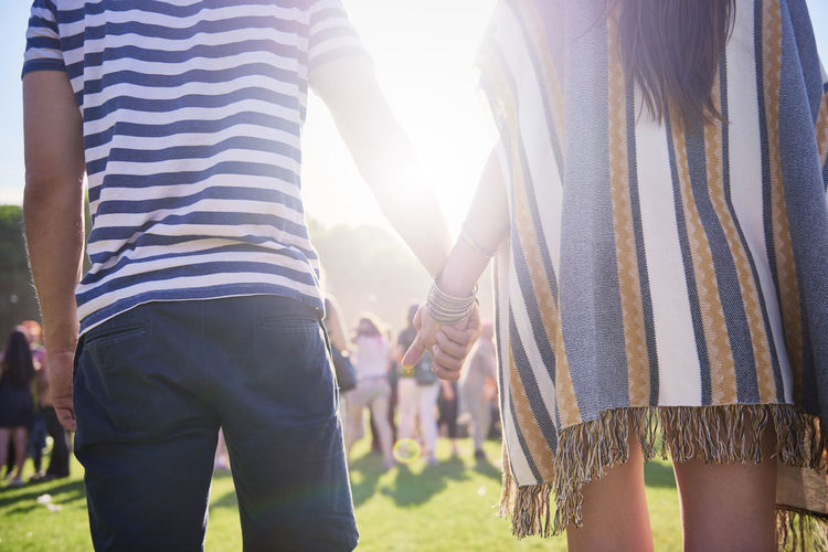 Rear view midsection of couple holding hands while standing on land during sunny day
