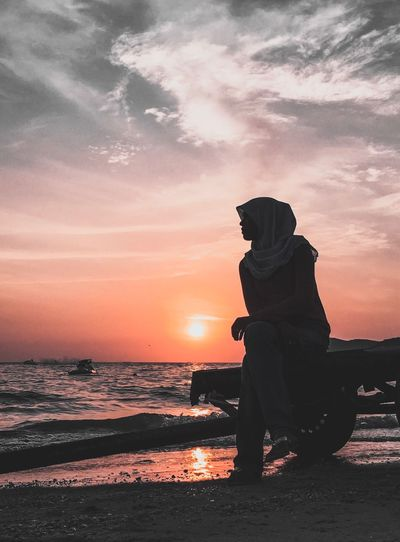 Woman Wearing Hijab Looking At Sea Against Sky During Sunset