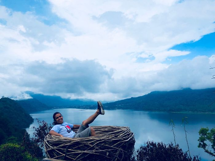 Portrait Of Man Sitting In Large Nest With Lake In Background Against Cloudy Sky