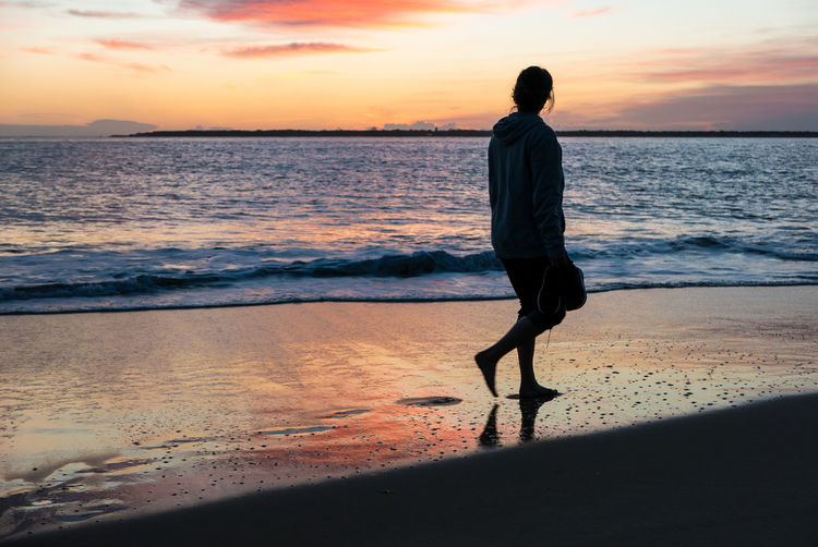 Full length of woman walking at beach during sunset