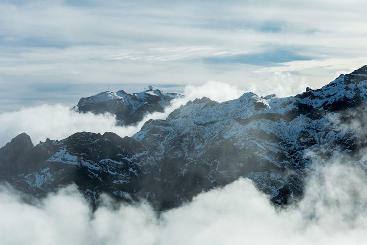 Overview of pico do areeiro peak covered with snow from pico ruivo footpath in madeira island