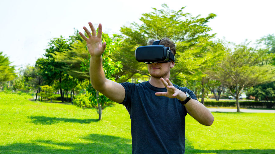 Man wearing virtual reality simulator while standing in park
