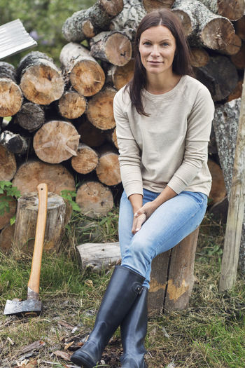 Portrait of a smiling young woman sitting on log