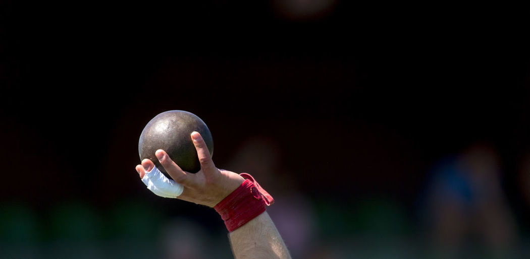 Cropped hand of athlete holding shot put