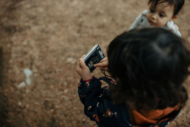 Rear view of boy photographing with mobile phone outdoors