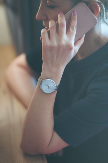 Elegant woman talking on mobile phone wearing silver wristwatch with bracelet and blue dress Calling Elegant Fashion Woman Wristwatch Adult Attitude Clock Clothing Formal Identity Lifestyles Looking Mobile One Person Outfit person Personal Phone Smart Phone Style Technology Time Watch Wearing