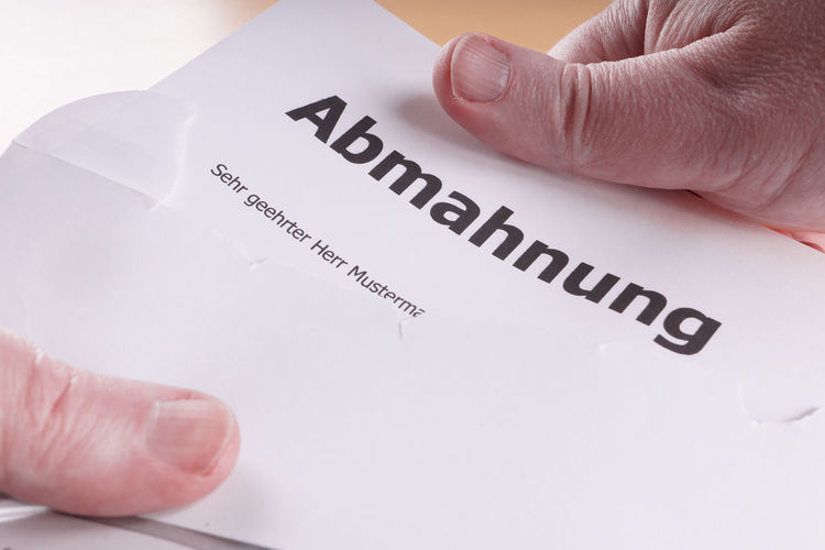 Abmahnung = German cease-and-desist letter Abgemahnt Abmahnung Abmahnwelle Brief Business Cease-and-desist Envelope Hands Law Legal Letter Office Open Opening Warning