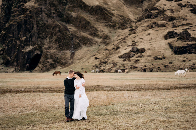 Rear view of couple standing on landscape