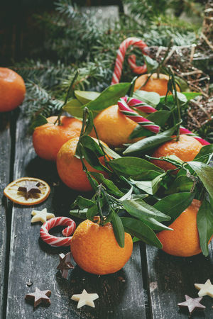 Tangerines with leaves in Christmas decor with Christmas tree, dry orange and candies over old wooden table. Natural day light. Dark rustic style Christmas Christmas Food Dark Orange Rustic Candy Christmas Tree Citrus Fruit Clementine Decoration Food Food And Drink Fruits Group Healthy Eating Leaf Leaves Table Tangerine Traditional Wooden