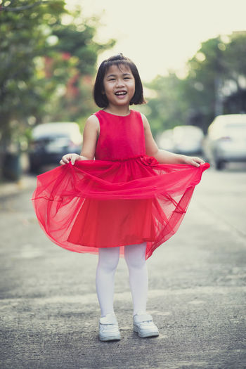 Full length portrait of smiling girl wearing red dress standing on road