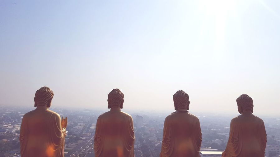 Buddha statue against clear sky during foggy weather