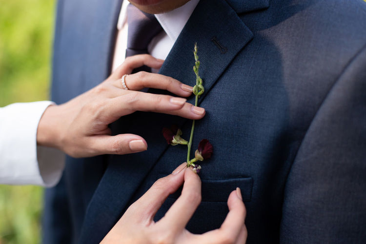 The bride touches a small bouquet for the groom. Human Hand Hand Midsection Men Holding Adult People Married Well-dressed Bridegroom Suit Human Body Part Love Day Bride Clothing Real People Wedding Nature Women Outdoors Wedding Ceremony Couple - Relationship Positive Emotion Love Together