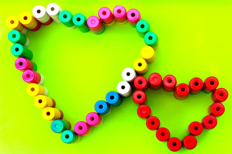 High Angle View Of Buttons Arranged In Heart Shape Over Colored Background