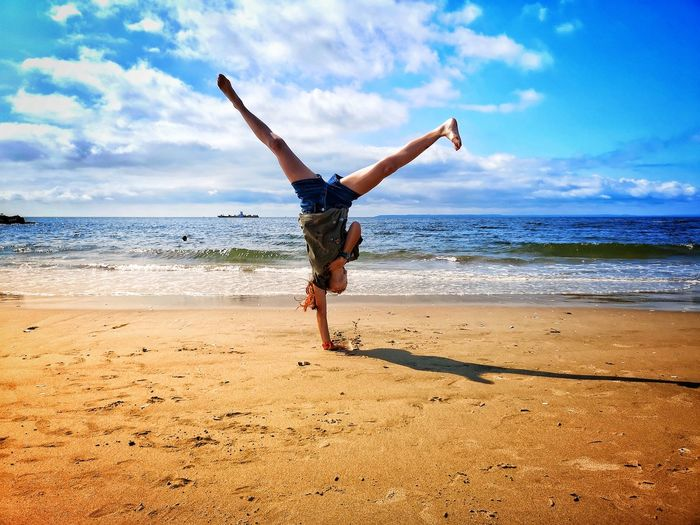 Full length of girl doing handstand on shore at beach