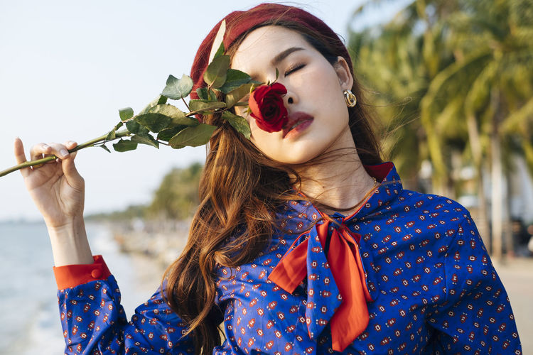Close-up of beautiful young woman holding rose standing on beach against sky