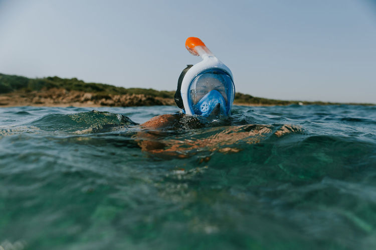 Close-up of bottle floating on sea against clear sky