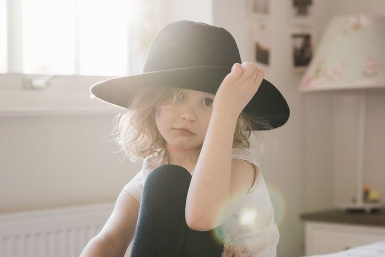 Portrait of cute girl wearing hat at home