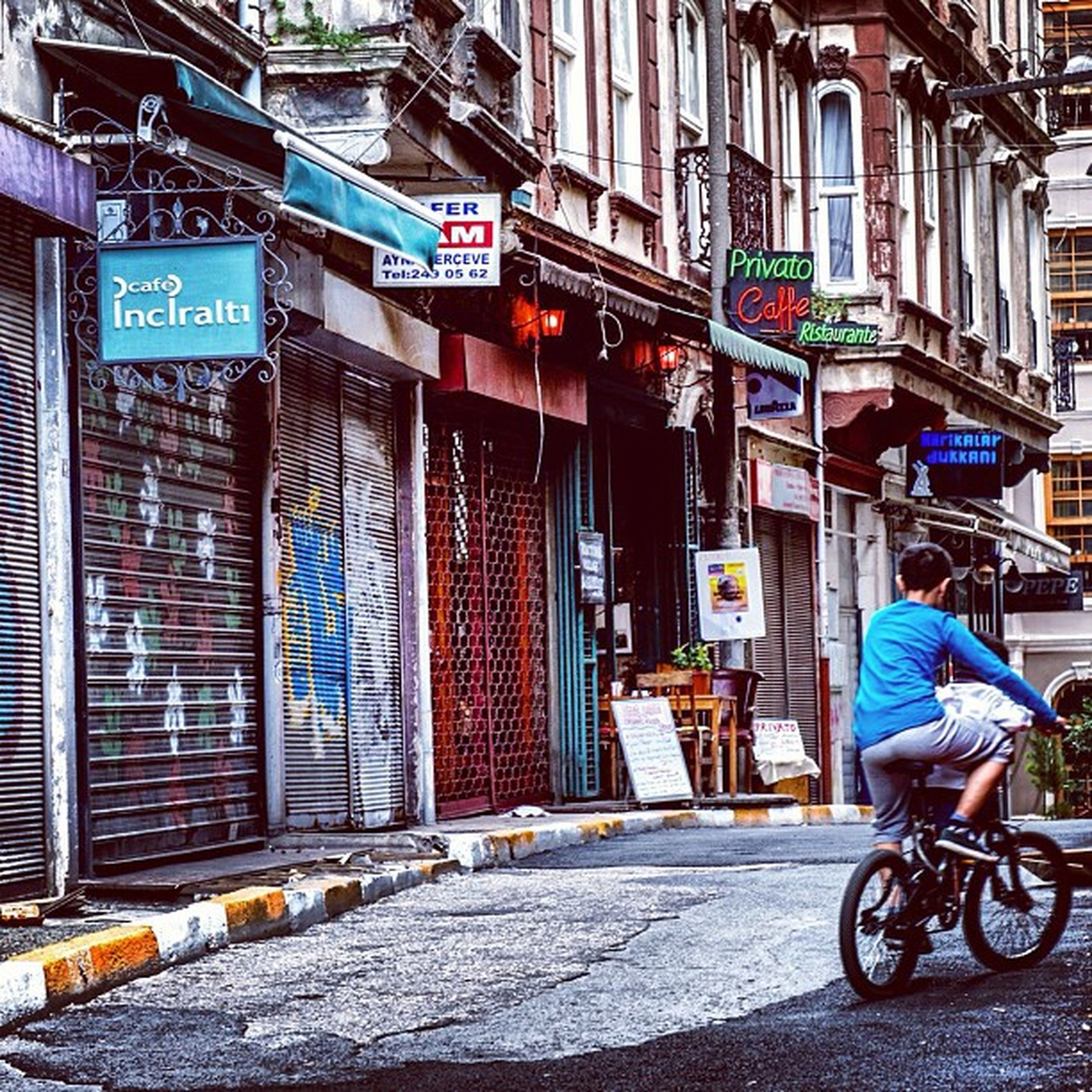 building exterior, architecture, bicycle, built structure, transportation, street, city, mode of transport, land vehicle, text, sidewalk, stationary, cobblestone, city life, building, parking, road, day