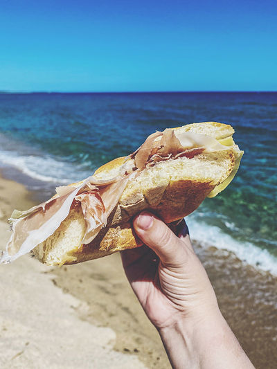 Midsection of person holding italian sandwich on beach