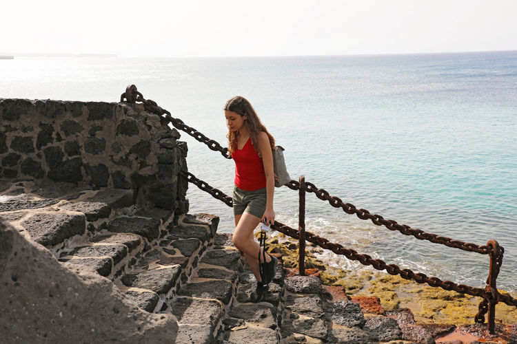 Woman Standing On Staircase Against Sea