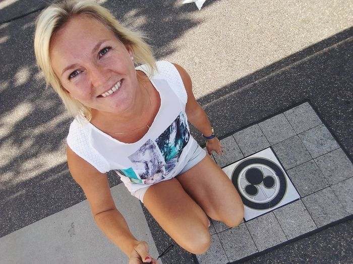 High Angle Portrait Of Smiling Young Woman Sitting On Footpath
