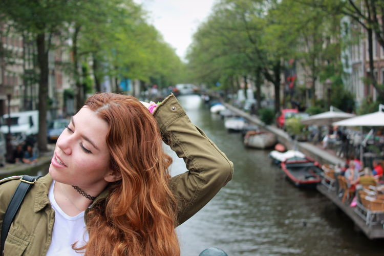 Young woman with arms raised in canal