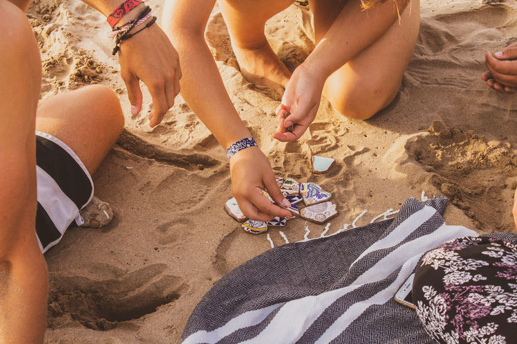 Woman With Friend Arranging Tiles On Sand At Beach