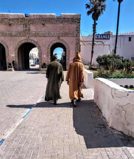 Two men wearing a traditional Djellaba gown with a qob (pointed hood) making their way to the medina walls in Essaouira, Morocco. Moroccan dress. Built Structure Architecture Rear View Building Exterior Full Length Two People Real People Women Walking Adult People Day Sunlight Footpath Nature Clothing City Men Street Lifestyles Outdoors Djellaba Moroccan Style Hood - Clothing Pointed Hood Qob Moroccan Dress The Art Of Street Photography