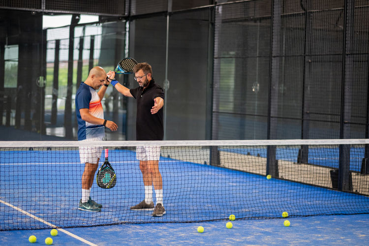 Monitor teaching padel class to man, his student - trainer teaches boy how to play paddle tennis