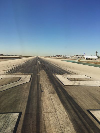 View of airport runway against clear blue sky