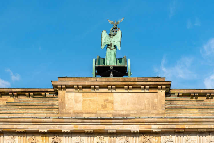 Low angle view of statue on building against sky