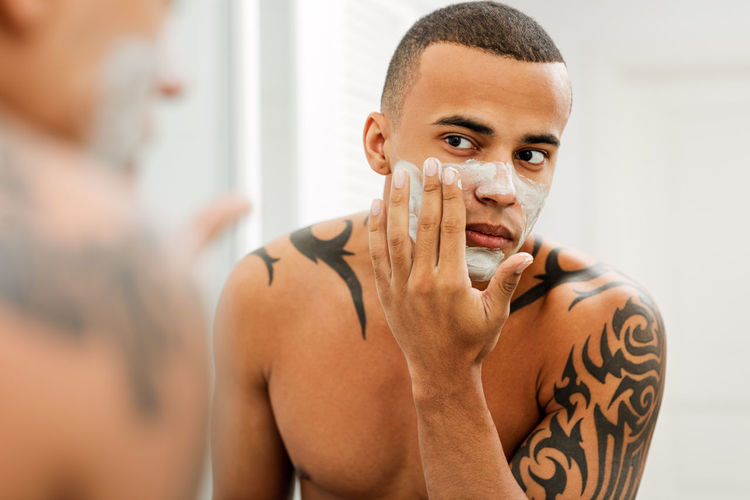 Lifestyles One Person Hygiene Portrait Cream Skin Care Applying Bathroom Indoors  Looking Mirror Reflection Handsome Males  Real People Body Care Indoors  Morning Routine