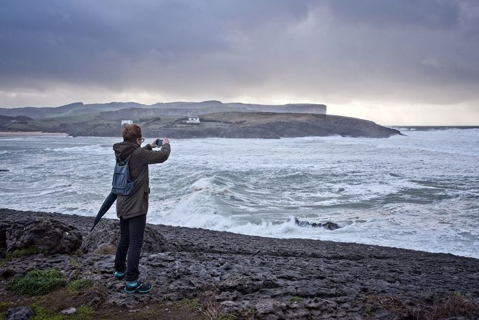 A woman takes pictures of the sea during the storm Alone Cantabria Lifestyle Photos Seashore Storm Surf Taking Photos Woman Ajo Backpack Bareyo Clouds Cuberris Ocean Outdoors Phone Rocks Sea Seascape Sky Smartphone Photography Tourism Umbrella Waves