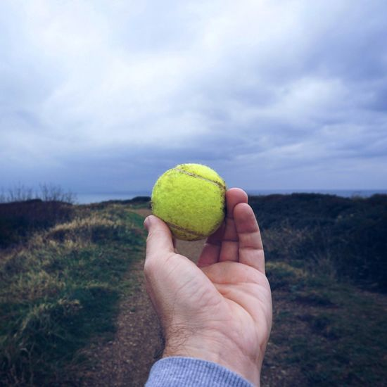 the tennis ball Human Hand Holding Hand Cloud - Sky Human Body Part One Person Real People Tennis Ball Yellow Sky Clouds Outdoors Nature Leisure Activity Day Focus On Foreground Land Food And Drink Lifestyles Personal Perspective Unrecognizable Person Body Part Finger