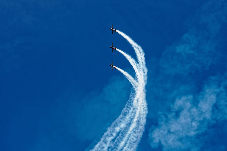 Aerobatics Air Vehicle Airplane Airshow Blue Clear Sky Day Fighter Plane Flying Formation Flying Low Angle View Mid-air Military Airplane Mode Of Transport Motion No People Outdoors Performance Sky Smoke - Physical Structure Speed Stunt Teamwork Transportation Vapor Trail