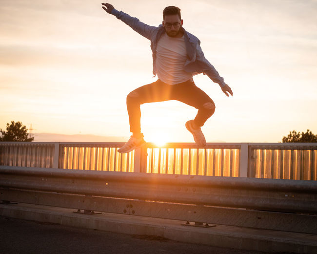 Man jumping on railing against sky during sunset